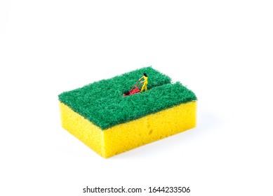 Miniature figure mowing lawn in a sponge