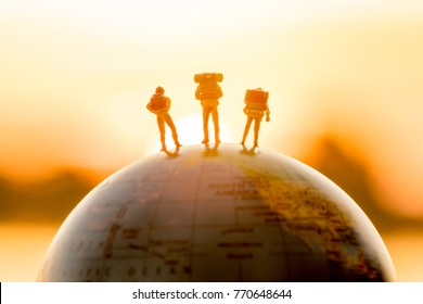 miniature figure people  backpack standing on globe with sunset or sunrise sky background