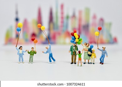 miniature figure people: Happy family  Catch balloons standding on white floor with blur city blackground. Picture use for holliday concept