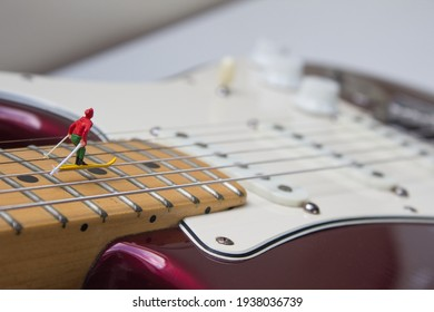 A miniature figure as a skier goes down on skis on the strings of an electric guitar. the pickups as well as switches and volume controls can also be seen