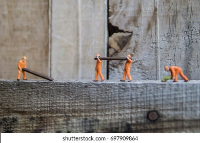 Miniature figure working in industrial - Close up of construction worker doing manual handling concept with selective focus.