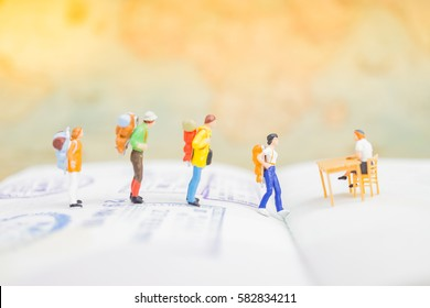 Miniature figures : Business man / traveler talking with immigration officer on passport with stamps. Success Business Due and Travelling agency concepts.