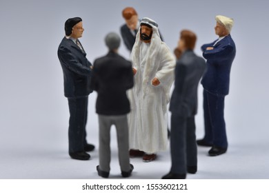 Miniature figures business people standing with Arab man. Arab man is standing in a circle of business men.