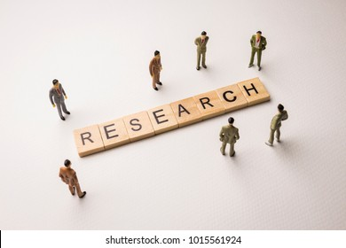 Miniature figures businessman : meeting on research letters by wooden block word on white paper background, in concept of business and corporation