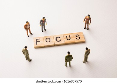 Miniature figures businessman : meeting on focus word by wooden block letters on white paper background, in concept of business and corporation