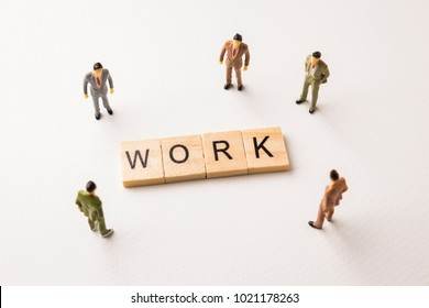 Miniature figures businessman : meeting on work word by wooden block letters on white paper background, in concept of business and corporation