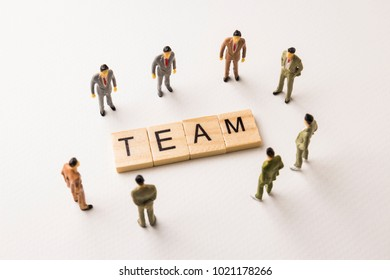 Miniature figures businessman : meeting on team word by wooden block letters on white paper background, in concept of business and corporation