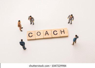 Miniature figures businessman : meeting on coach letters by wooden block word on white paper background, in concept of business and corporation