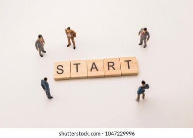 Miniature figures businessman : meeting on start letters by wooden block word on white paper background, in concept of business and corporation