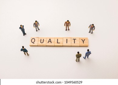 Miniature figures businessman : meeting on quality letters by wooden block word on white paper background, in concept of business and corporation