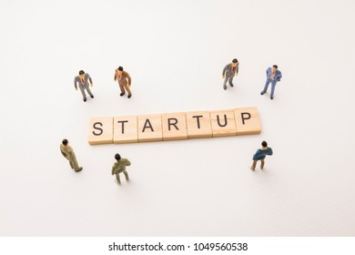 Miniature figures businessman : meeting on startup letters by wooden block word on white paper background, in concept of business and corporation