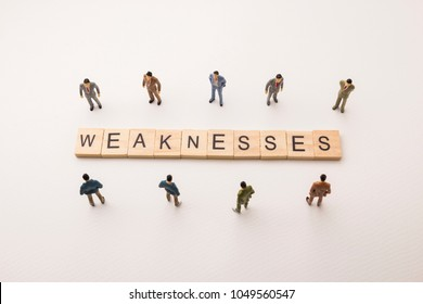 Miniature figures businessman : meeting on weaknesses letters by wooden block word on white paper background, in concept of business and corporation