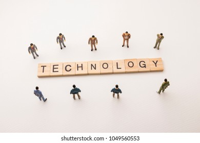 Miniature figures businessman : meeting on technology letters by wooden block word on white paper background, in concept of business and corporation