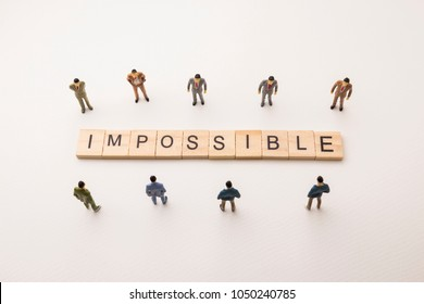 Miniature figures businessman : meeting on impossible letters by wooden block word on white paper background, in concept of business and corporation