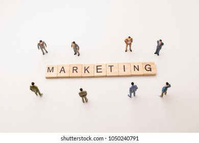 Miniature figures businessman : meeting on marketing letters by wooden block word on white paper background, in concept of business and corporation