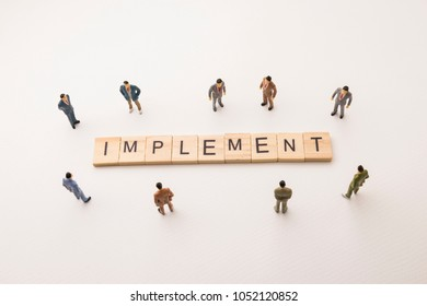 Miniature figures businessman : meeting on implement letters by wooden block word on white paper background, in concept of business and corporation