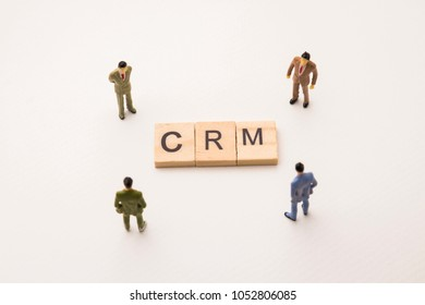 Miniature figures businessman : meeting on crm letters by wooden block word on white paper background, in concept of business and corporation