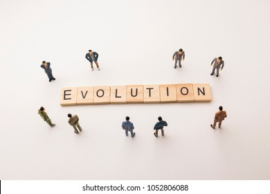 Miniature figures businessman : meeting on evolution letters by wooden block word on white paper background, in concept of business and corporation
