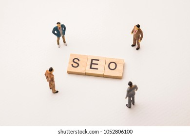 Miniature figures businessman : meeting on seo letters by wooden block word on white paper background, in concept of business and corporation