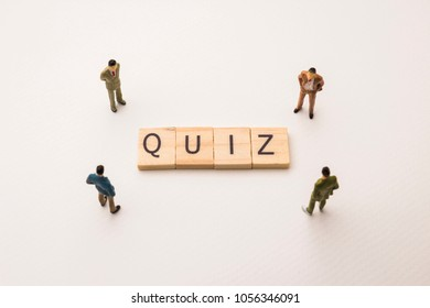 Miniature figures businessman : meeting on quiz letters by wooden block word on white paper background, in concept of business and corporation