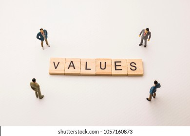 Miniature figures businessman : meeting on values letters by wooden block word on white paper background, in concept of business and corporation
