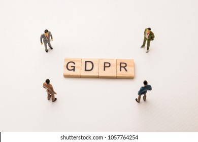 Miniature figures businessman : meeting on GDPR letters by wooden block word on white paper background, in concept of business and corporation