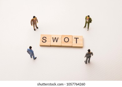 Miniature figures businessman : meeting on SWOT letters by wooden block word on white paper background, in concept of business and corporation