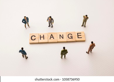Miniature figures businessman : meeting on change word by wooden block word on white paper background, in concept of business and corporation