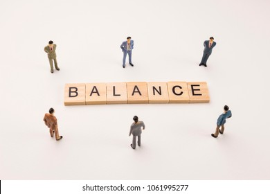 Miniature figures businessman : meeting on balance word by wooden block word on white paper background, in concept of business and corporation
