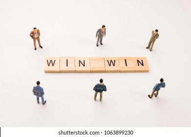 Miniature figures businessman : meeting on win win word by wooden block word on white paper background, in concept of business and corporation