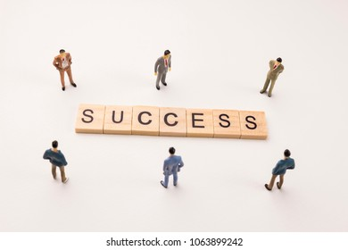 Miniature figures businessman : meeting on success word by wooden block word on white paper background, in concept of business and corporation