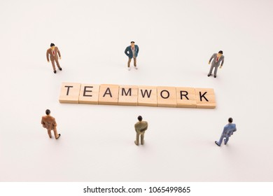 Miniature figures businessman : meeting on teamwork word by wooden block word on white paper background, in concept of business and corporation