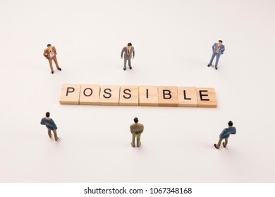 Miniature figures businessman : meeting on possible word by wooden block word on white paper background, in concept of business and corporation