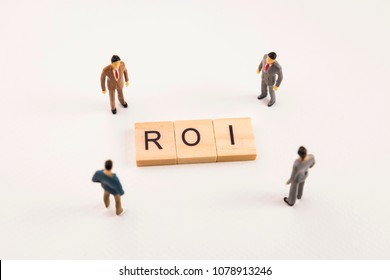 Miniature figures businessman : meeting on roi letters by wooden block word on white paper background, roi is acronym from word return on investment.