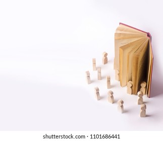 Miniature figures of people come out of the book into the real world. The book comes alive, the characters come out of the book into the real world. The concept of adventure. Propaganda reading books