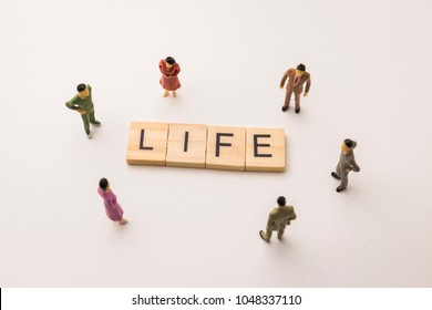 Miniature figures people : meeting on life letters by wooden block word on white paper background, in concept of diversity