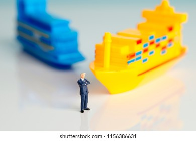 Miniature figures of a successful businessman with shipping background.