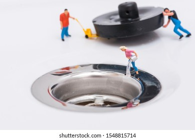 Miniature figures wasting water to the sinkhole