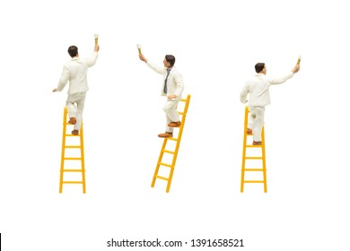 Miniature figurine character as painter standing on wooden ladder and painting wall with paint tools isolated on white background.