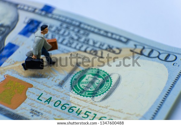 Miniature figurine concept : The businessman traveling on 100 US Dollars, business travel or marketing, financial economy, global internet online finance and other marketing concepts.