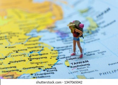 Miniature figurine concept : Female young traveler traveling / standing on TAIWAN in Asia map travel around the world, business trip traveler adviser agency or online world wide marketing concept.