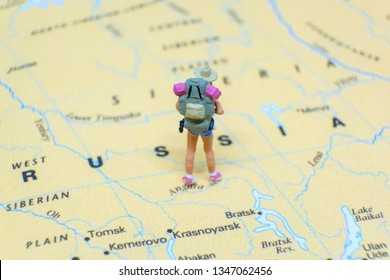 Miniature figurine concept : The young traveler traveling / standing on RUSSIA map travel around the world, business trip traveler adviser agency or online world wide marketing concept.