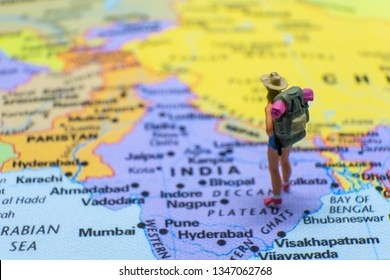 Miniature figurine concept : The young traveler traveling / standing on INDIA map travel around the world, business trip traveler adviser agency or online world wide marketing concept.