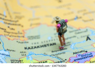 Miniature figurine concept : The young traveler traveling / standing on KAZAKHSTAN in Asia map travel around the world, business trip traveler adviser agency or online world wide marketing concept.