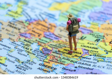 Miniature figurine concept : The young traveler traveling / standing on EUROPE map travel around the world, business trip traveler adviser agency or online world wide marketing concept.