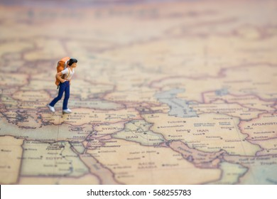 Miniature figurine of lonely  young traveler walking  on big map