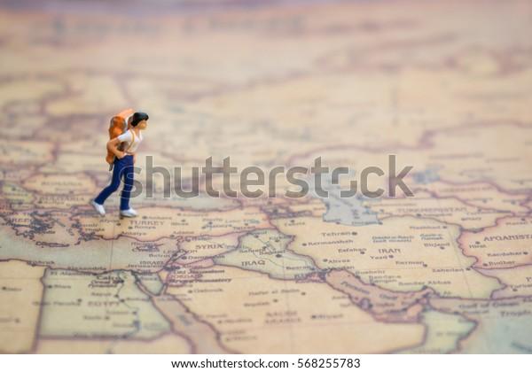 figurine miniature du jeune voyageur solitaire marchant sur une grande carte