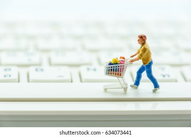 Miniature figurine : a male shopper pushes a shopping cart on a space bar on white keyboard. Concept of brick and mortar stores nowadays face with increased competition from internet online ecommerce.