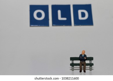 miniature figurine of an old man sitting on a bench