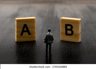 Miniature figurine posed as businessman making decision on Solution A versus B, minimalist abstract concept image